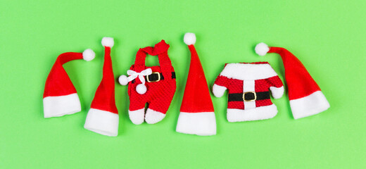 Wall Mural - Top view of red Santa hats and clothes on colorful background. Banner Merry Christmas concept with copy space