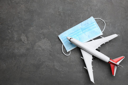 Toy airplane and protective mask on grey background, flat lay with space for text. Travelling during coronavirus pandemic