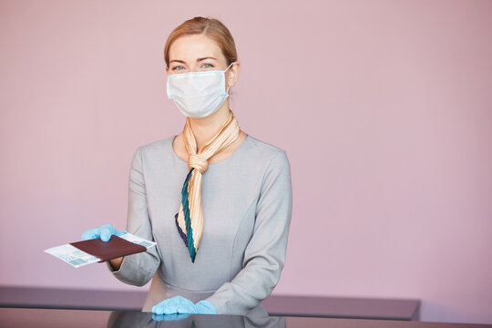 Waist up portrait of blonde flight attendant wearing mask while standing at check in desk handing tickets to passenger, copy space