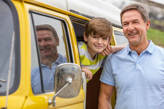 Happy Middle Aged Man Father and Son With Camper Van Bus