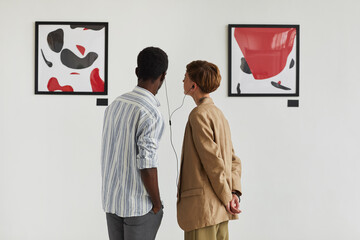 Graphic back view portrait of two young people looking at paintings and sharing audio guide while...
