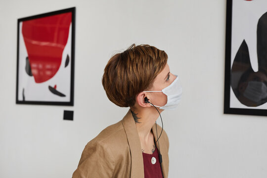 Side view portrait of young woman looking at paintings and wearing mask at modern art gallery exhibition, copy space
