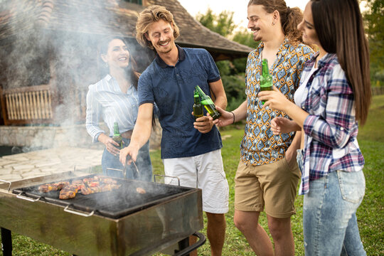 Group of four young people making a barbeue