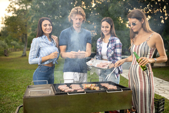 Group of friends putting some meat on barbecue