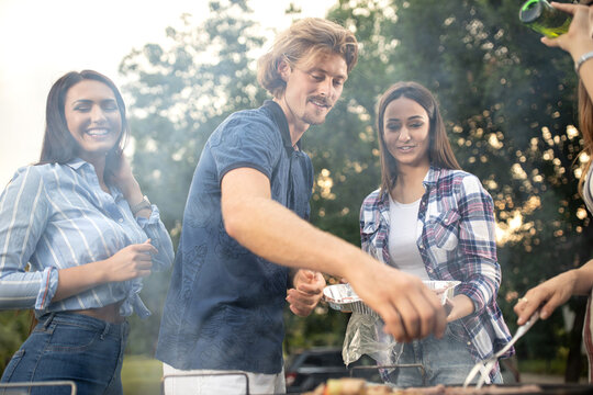 Young people preparing a barbecue in the back yard