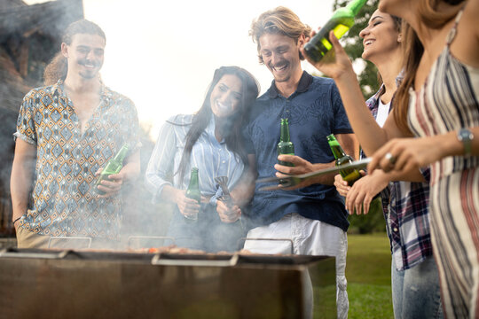 Friends making outdoor meal on a barbeque