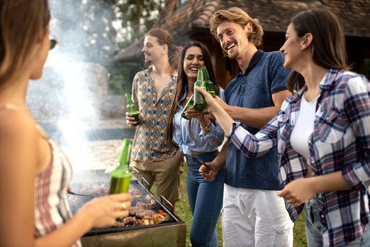 Group of friends chilling with beer as they prepare barbeque