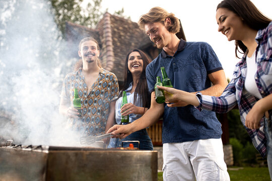 Young people roasting meat as it smokes all over the barbecue
