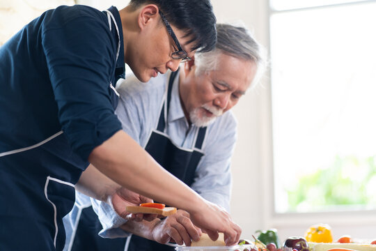 Happy Asian family. Elderly Asian father and Adult son cooking in the kitchen. Indoors at home.
