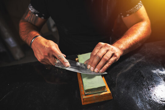 Man's hands sharpening knife