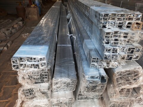 Anodized aluminium metal frames wrapped in polythene in a factory