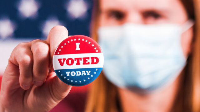Woman with face mask showing I voted today button with american flag. Extreme close-up