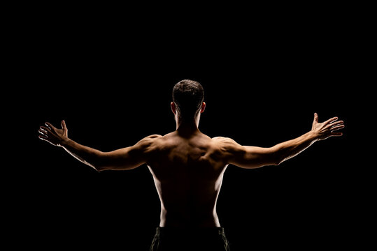 Rear view of muscular man with outstretched arms isolated on black background.