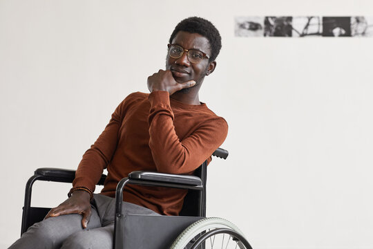 Minimal portrait of young African-American man using wheelchair and looking at camera while posing in modern art gallery, copy space