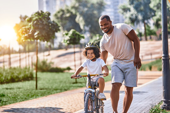 Cheerful curly kid cycling with his father by his side
