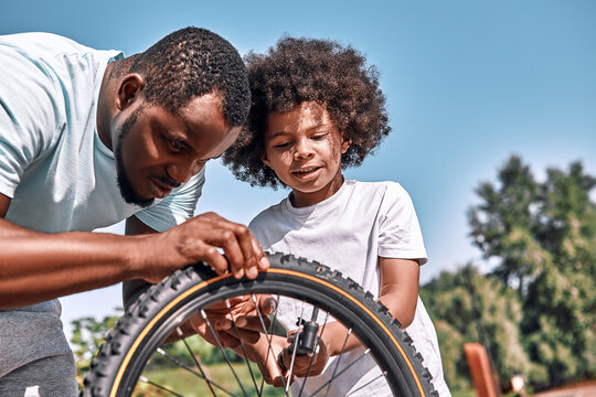 Responsible father fixing a flat tyre of his son bike