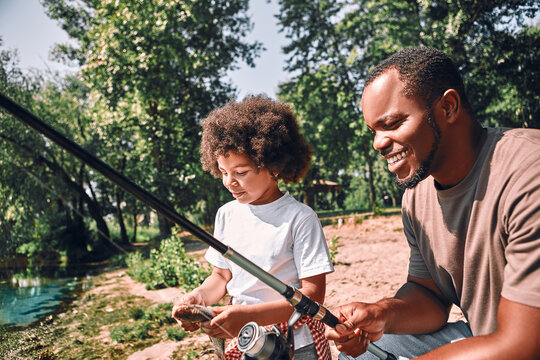 Happy child and his dad fishing on beautiful day outdoors