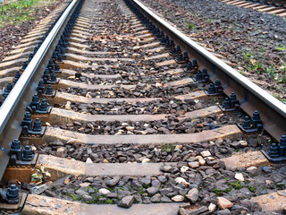low view of rails of railroad track with concrete sleepers in Moscow region in evening