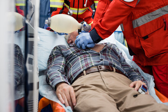Selective focus of paramedics doing cardiopulmonary resuscitation with bag valve mask to sick patient during first aid