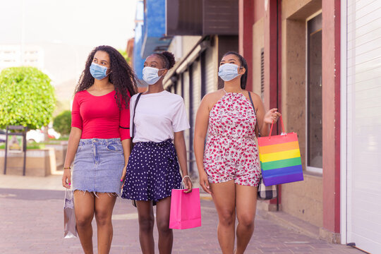 Friendship shopping with protective masks for coronavirus. A picture of girls with shop bags. Shopping, tourism and virus concept.
