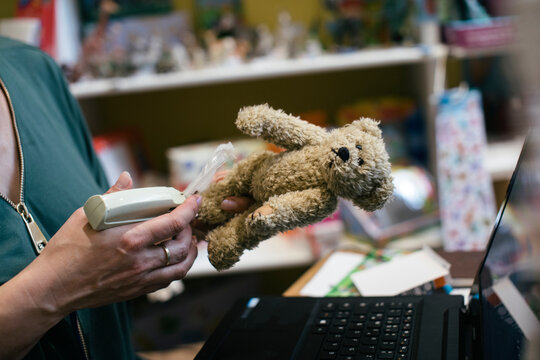Toy Shop Owner Putting Price Tag On Stuffed Bear