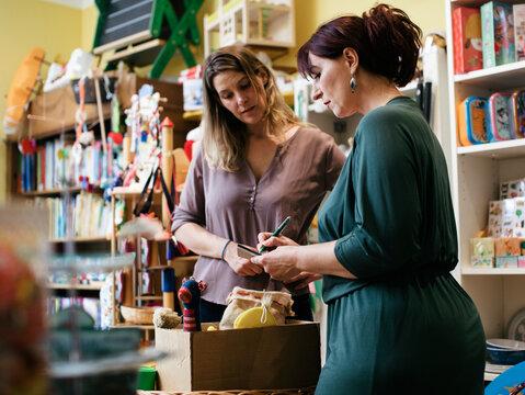 Toy Shop Owner Preparing Receipt For Customer