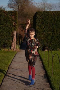 Boy wearing dress and heels dances along a garden path.