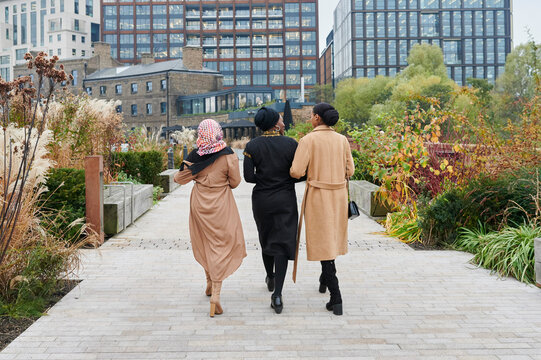 Three Muslim women walking in a park