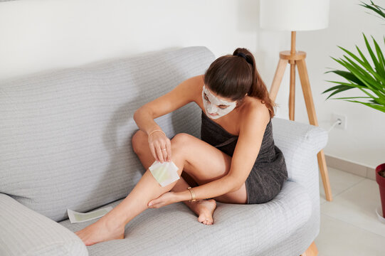 Woman waxing her legs on a sofa