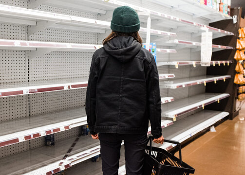 Person holding basket staring at empty grocery store shelves during the Coronavirus pandemic
