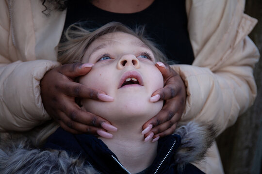 A black girl with long nails caresses the face of a young white girl.