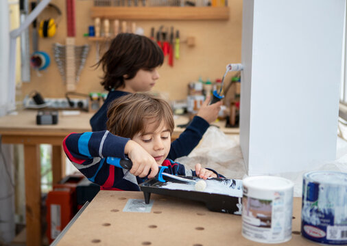 Five year old boy with his nine year old brother painting a wooden box