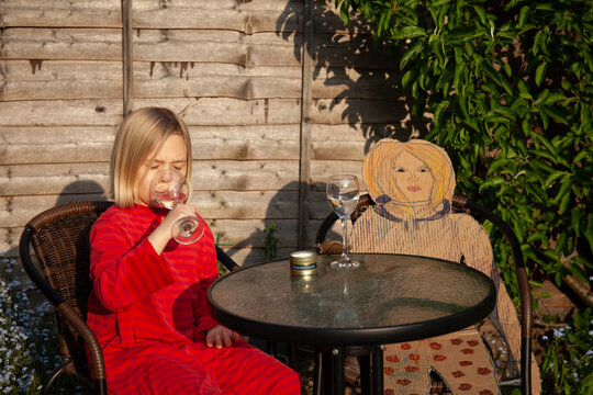 Little girl in a pretend cafe with a cardboard friend.