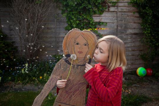 Blowing dandelion clocks with a pretend cardboard friend.