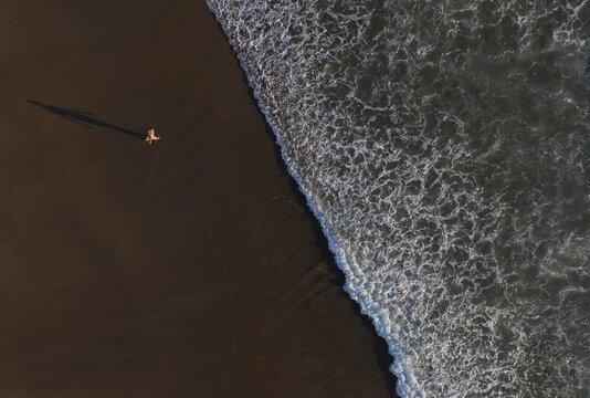 Persons shadow walking on a Black Beach in Bali