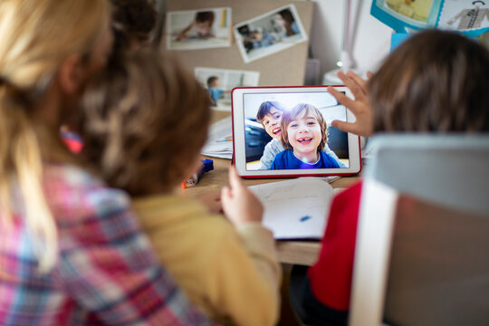 Mother and her kids doing video chat with their friends