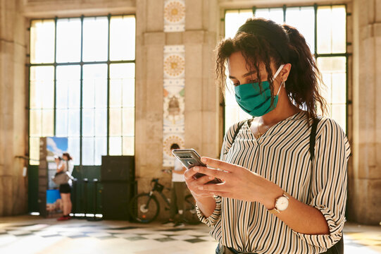 Woman wearing a face mask texting in a station