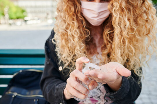 Woman in a face mask using hand sanitizer outside