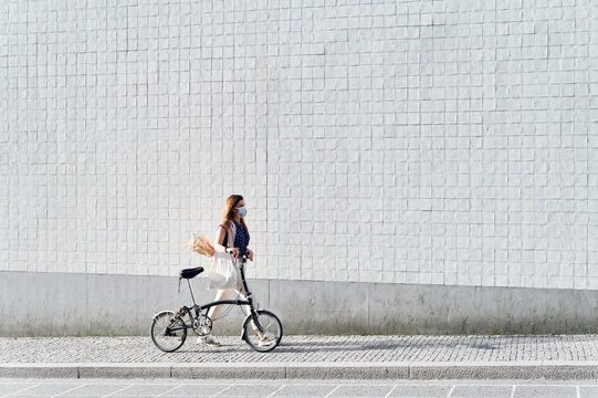 Woman in a face mask walking with a bike