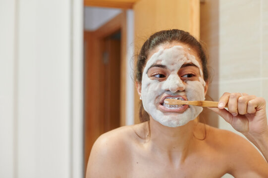 Woman brushing her teeth in a mirror