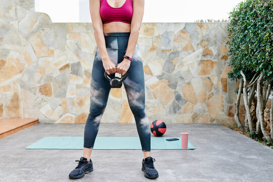 Fit woman lifting weights outside