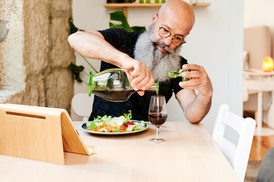 Man pouring a glass of wine at dinner