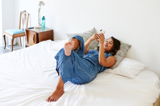 Smiling woman using a cellphone on her bed