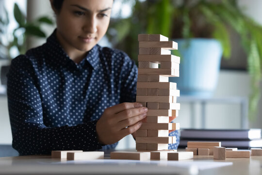 Close up of concentrated smart young Indian woman sit at desk in office brainstorm play wooden stack game alone. Focused serious ethnic female engaged in logical strategic thinking at workplace.