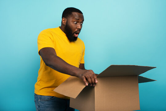 Happy boy receives a package from online shop order. happy and surprised expression. Blue background.