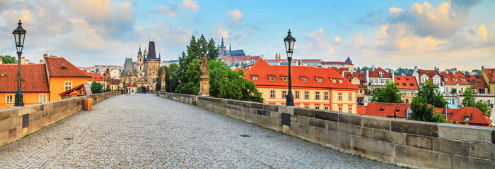 City summer landscape at sunrise - view of the Charles Bridge in historical district of Prague, Czech Republic