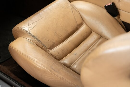 Old cracked damaged leather on car leather upholstery.
