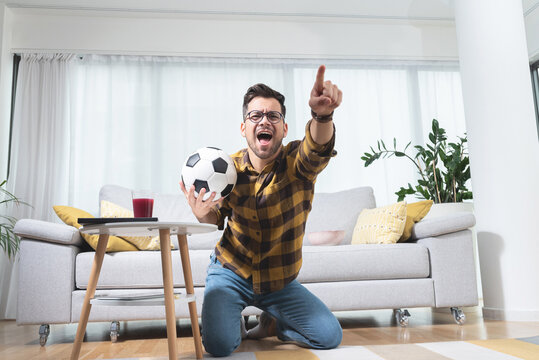 Football fan celebrating victory at home