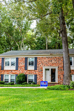 Sterling, USA - September 15, 2020: Presidential election political sign poster in support of Joe Biden 2020 text in northern Virginia suburbs with brick house exterior in neighborhood