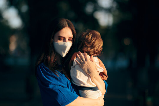Worried Mother Wearing Face Mask Holding her Child